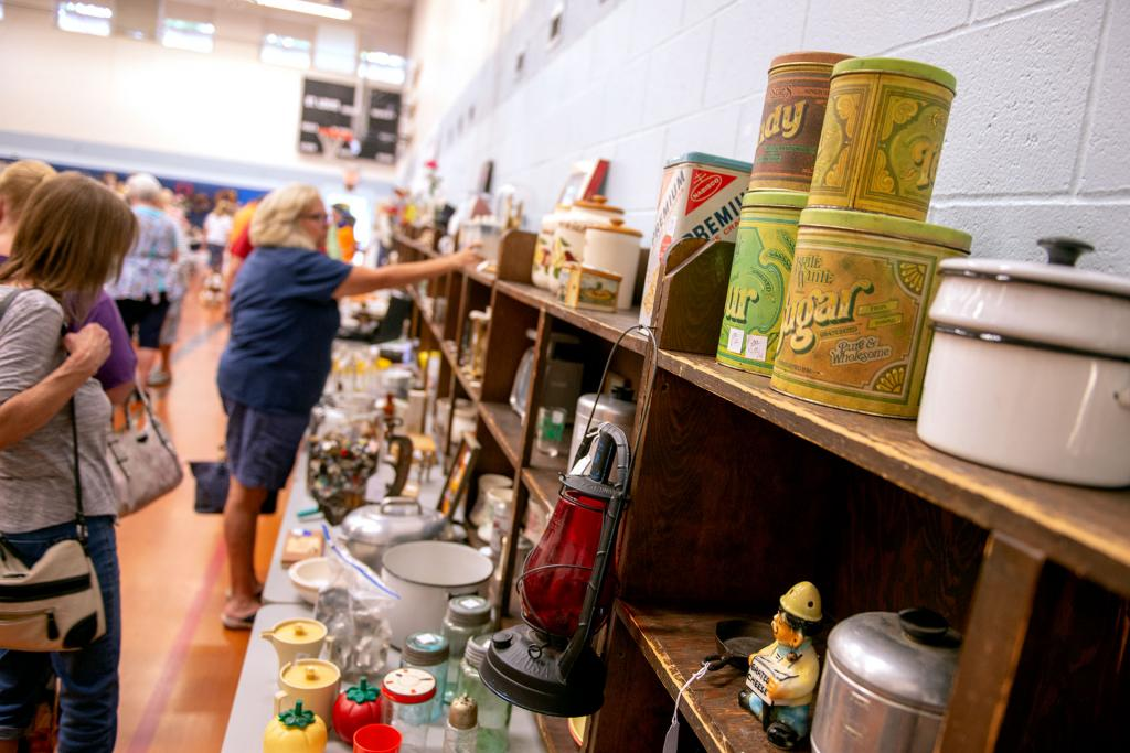 Visitors examine household items for sale.