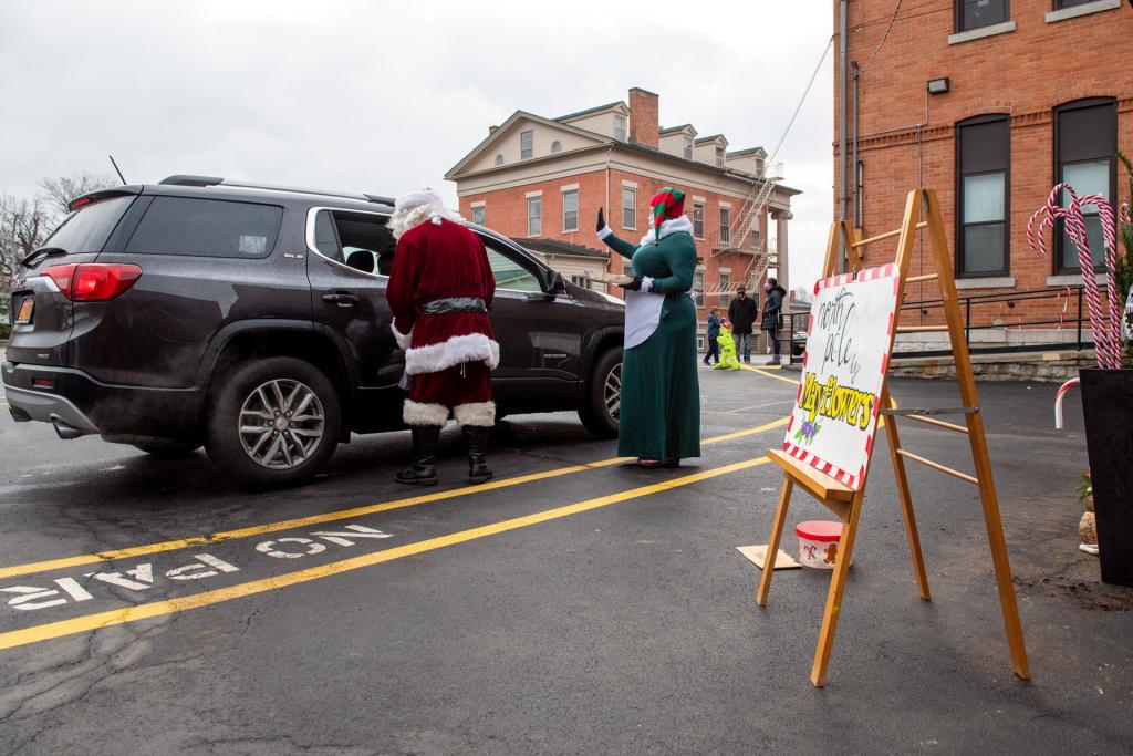 Santa and Mrs. Claus speak to children through a car window.