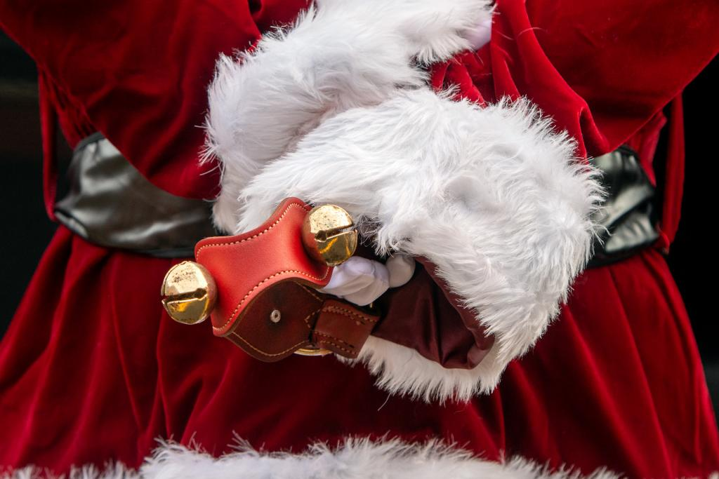 Santa holds jingle bells behind his back.
