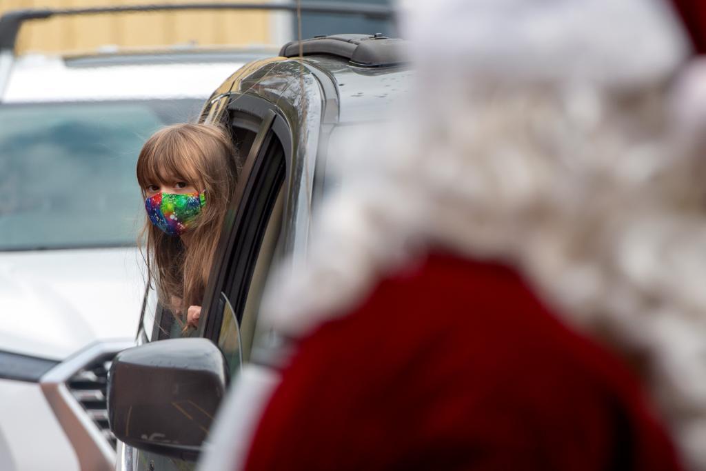 Kindergartner Cathryn Parker hangs out of her car window before seeing Santa.