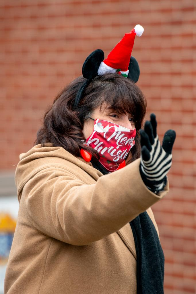 St. Mary School Principal Lisa Milano waves to students as they drive by.