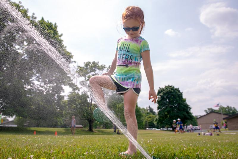 St. Joseph School kindergartner Emma Thomas rinses off her feet under the sprinkler.