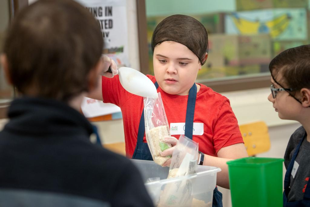 Colin Von Bevern, a fifth-grader at St. Mary Our Mother School in Horseheads, loads packages of rice while volunteering at Food Bank of the Southern Tier Jan. 29 as part of Catholic Schools Week activities.