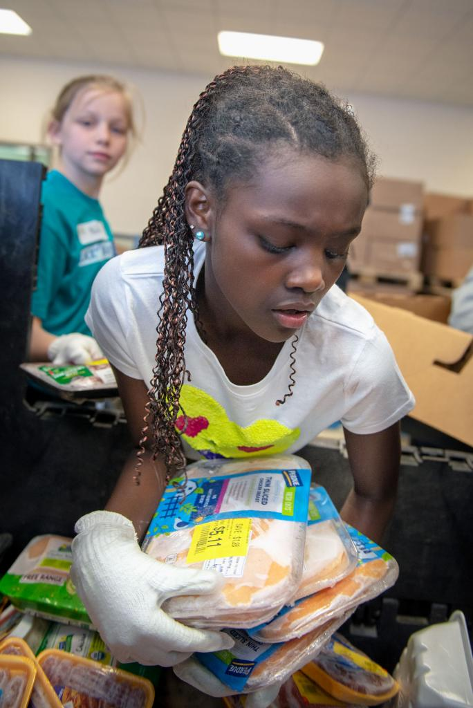 Kira Alsworth, a sixth-grader at St. Mary Our Mother School in Horseheads, sorts frozen foods while volunteering at Food Bank of the Southern Tier Jan. 29.