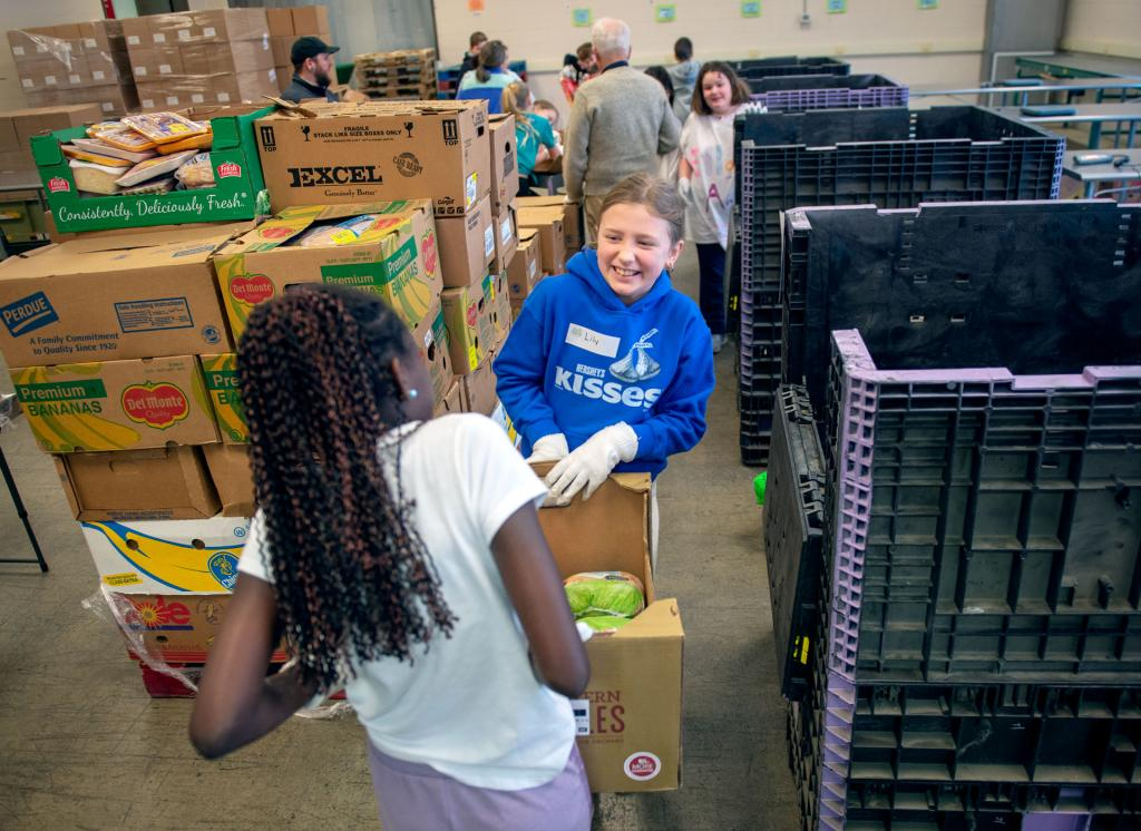 St. Mary Our Mother School students Kira Alsworth (left) and Ellie Green (right) carry a box of frozen foods to be sorted at Food Bank of the Southern Tier Jan. 29.