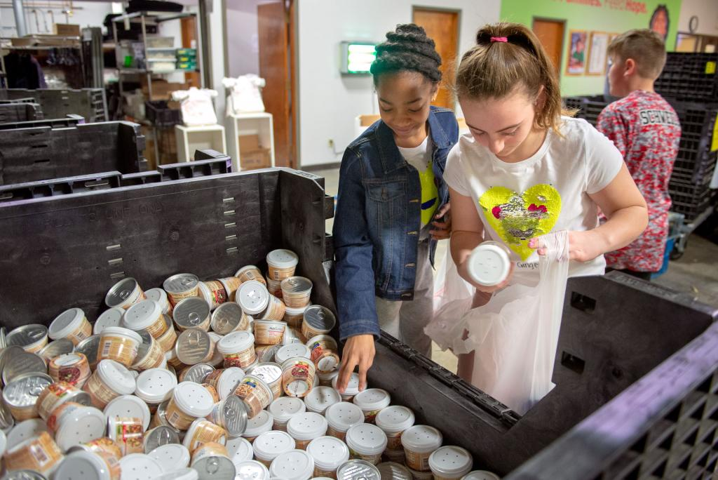 St. Mary Our Mother students Sophia Toribio (left) and Ginger Curione fill grocery bags with canned goods at Food Bank of the Southern Tier Jan. 29.