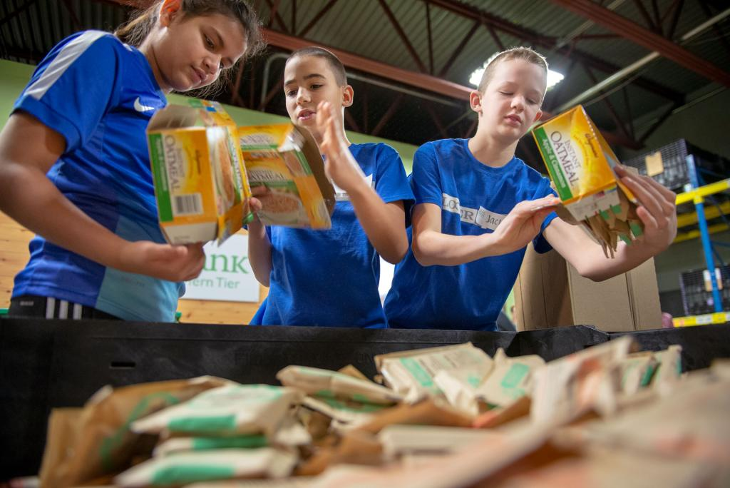 Jessica Als (from left) Miles Woodhouse, Jack Fesetch, students at St. Mary Our Mother School in Horseheads, empty boxes of oatmeal into a bin Jan. 29 while volunteering at Food Bank of the Southern Tier.