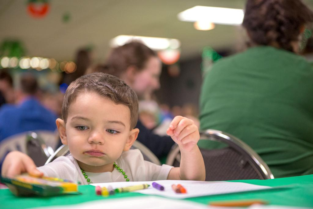 Two-year-old Jerry Reyes colors a picture before dinner during the annual St. Patrick's Day celebration at St. Paul of the Cross Church in Honeoye Falls March 10. (Courier photo by Jeff Witherow)