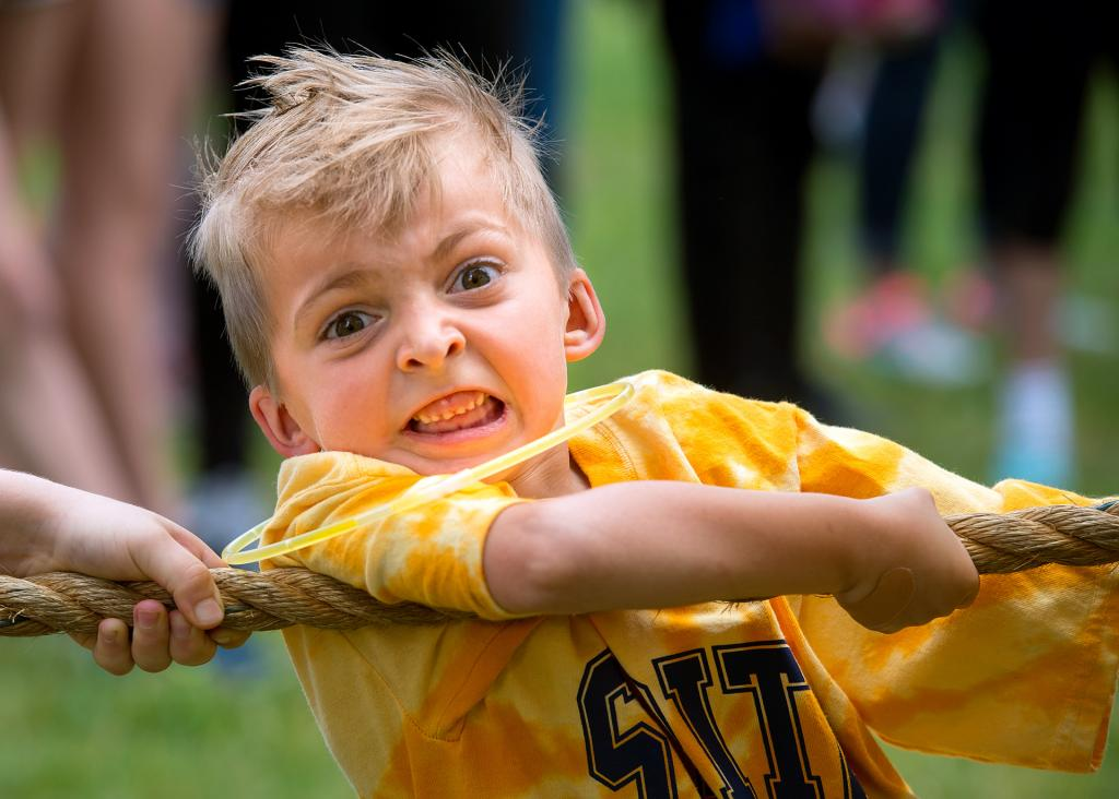 First-grader Liam Williams participates in a tug-of-war contest June 21 during the Blue-Gold Day at Webster's St. Rita School. The field day event marked the last day of school for the students.