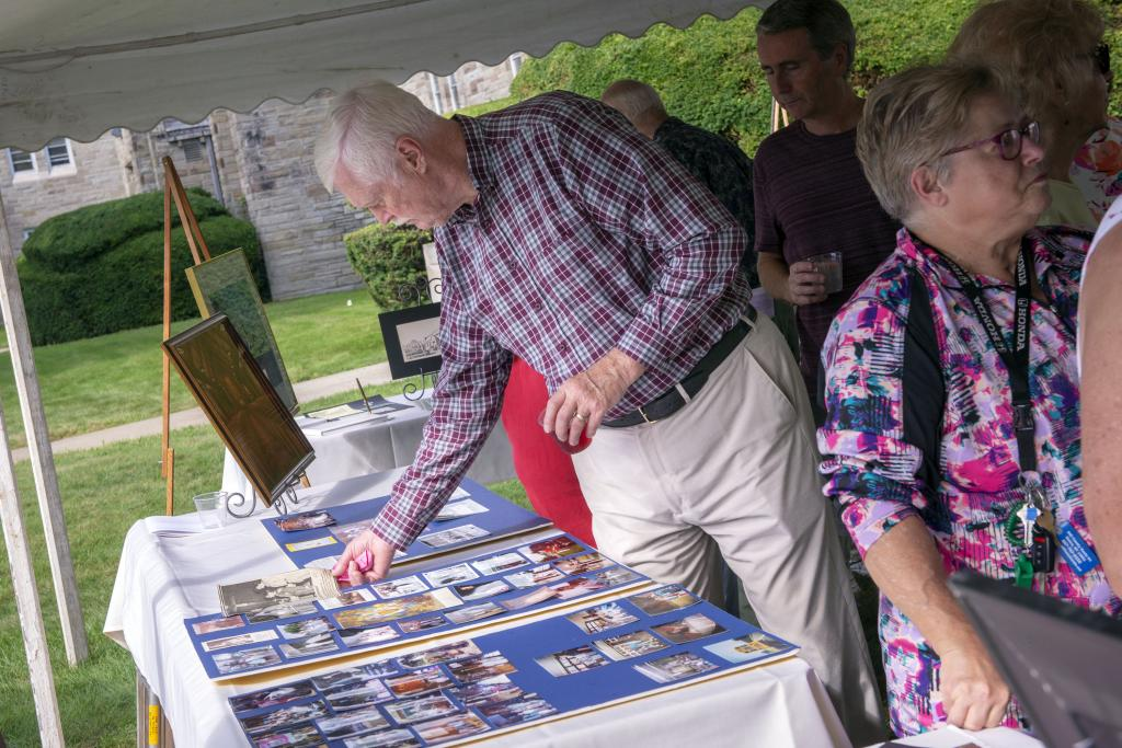 Peter Roberts looks over an array of photos of time spent at the church. (Courier photo by Jeff Witherow)