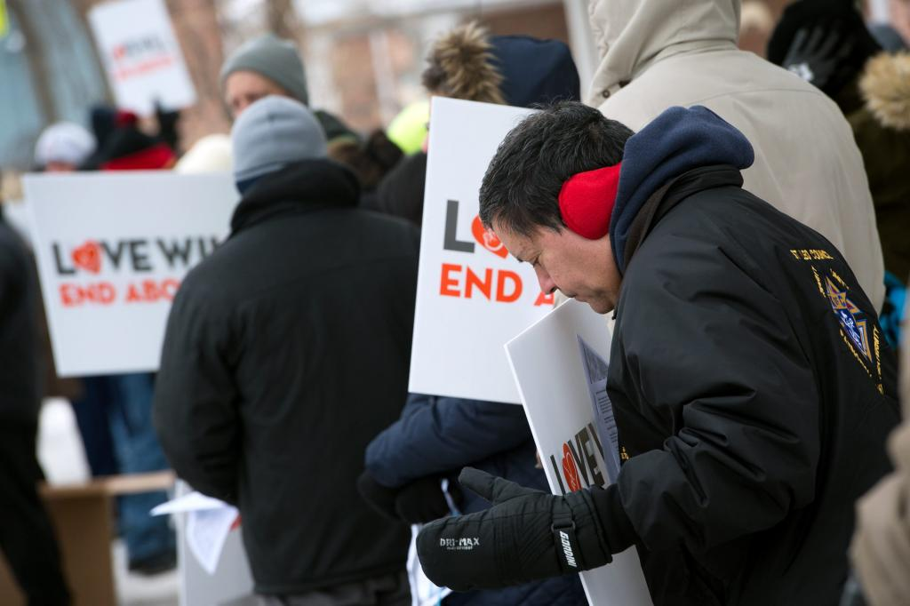 José Rivera stands with protesters outside of a Planned Parenthood location in Rochester Dec. 16.