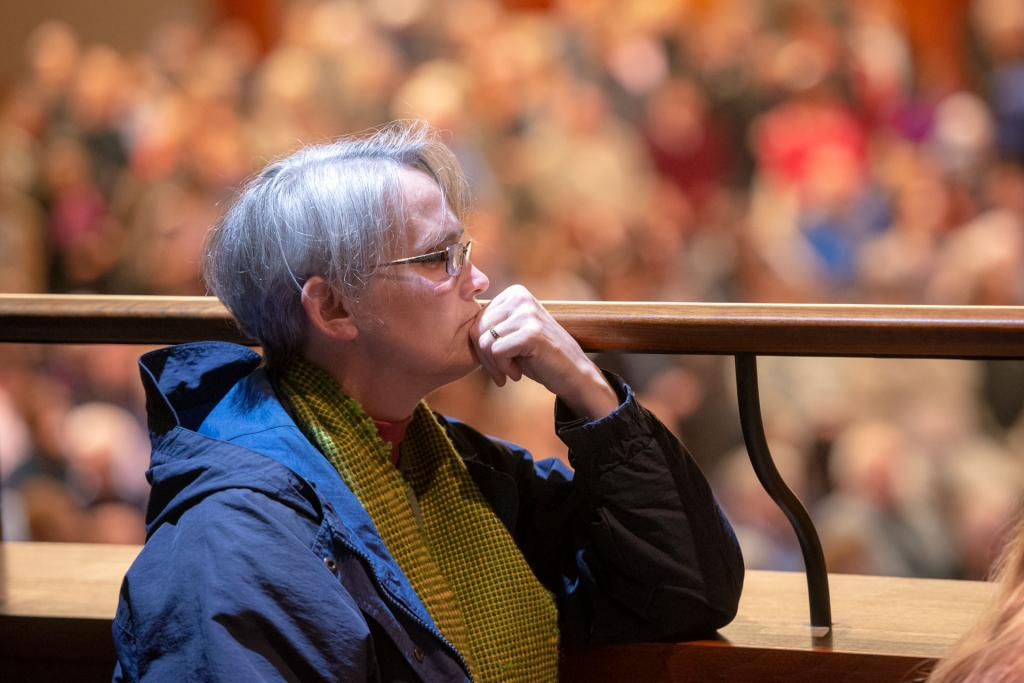 A vigil participant listens to speakers from the balcony of Temple B'rith Kodesh.