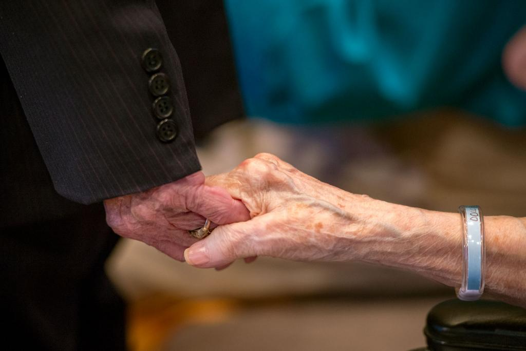 Bob and Dee Crowell, who have been married 69 years, hold hands during the Mass.