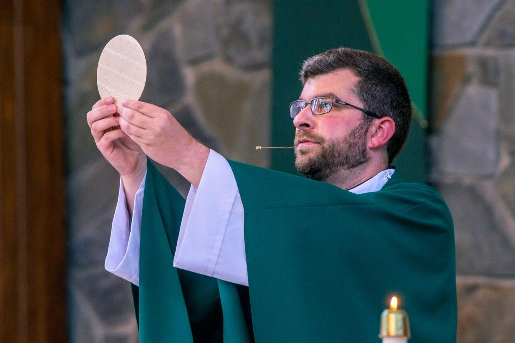 Father Downer elevates the Eucharist.
