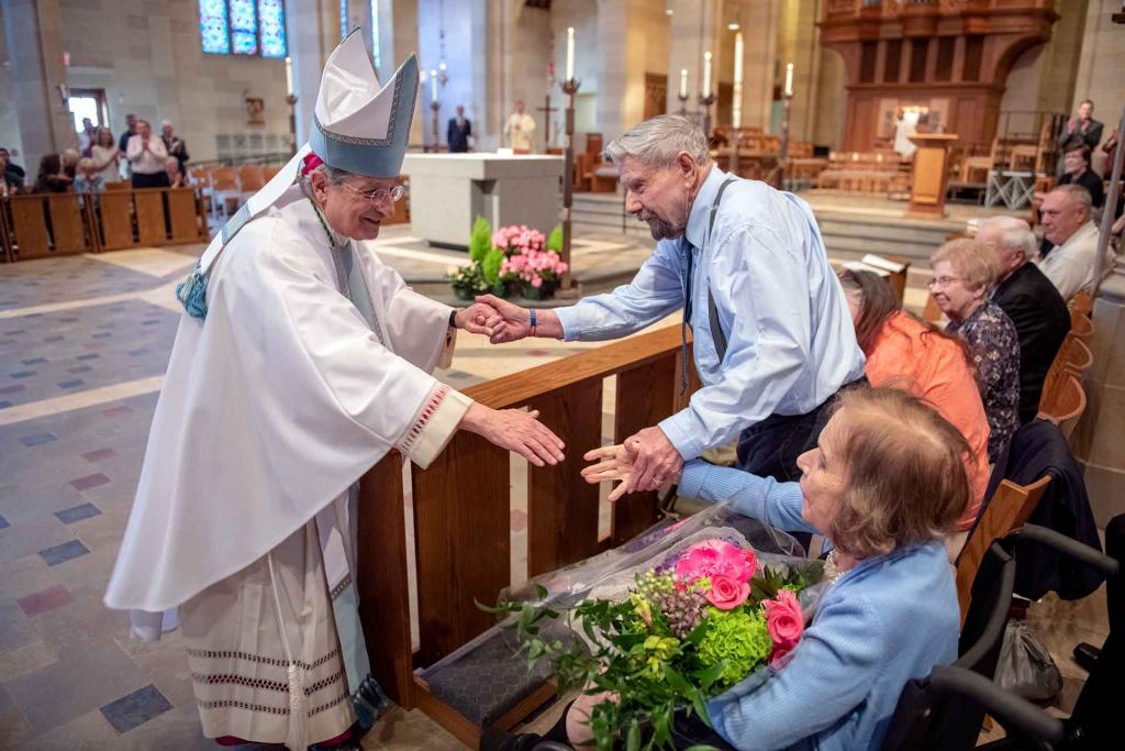 During the Marriage Recognition Mass at Sacred Heart Cathedral May 19, Bishop Salvatore R. Matano congratulates the longest-married couple in attendance, Robert and Dolores Crowell, who are celebrating their 70th wedding anniversary this year.