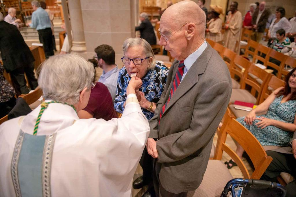 Jeanne Sweeney and her husband, Dr. Thomas Sweeney, receive Communion from Bishop Matano.