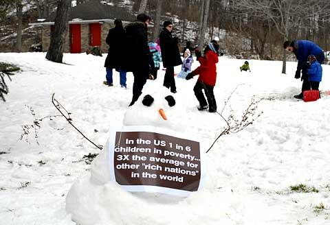 An informative sign adorns one of the snowmen.