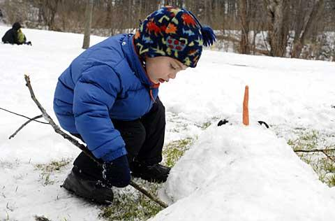 Three-year-old Ryan Hurwitz adds arms to his snowman.