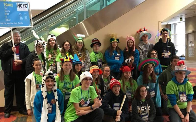 Father Michael Schramel and youth from the Parish of the Holy Family in Gates pose for a photo in the Indiana Convention Center. (Photo courtesy of The Parish of the Holy Family)