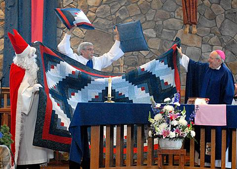 Bishop Emeritus Clark shows off his new quilt.