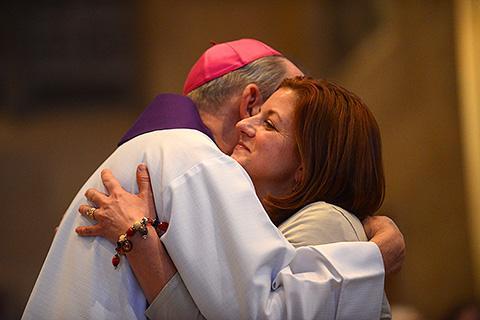 The bishop hugs candidate Kristine McCarthy.
