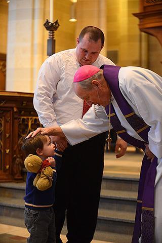 The bishop greets 3-year-old Ryan Simonds.