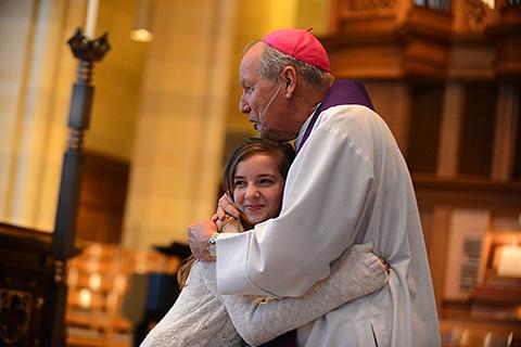 12-year-old catechumen Audrey Forte gets a hug from Bishop Clark.