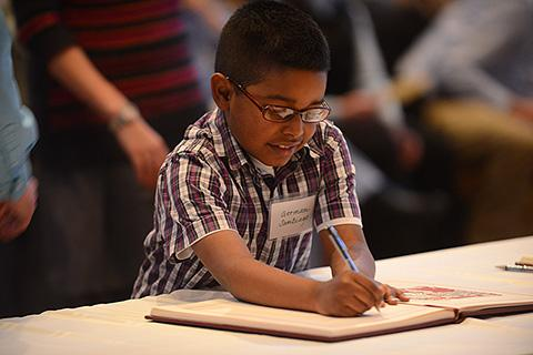 7-year-old German Santiago signs the Book of the Elect.