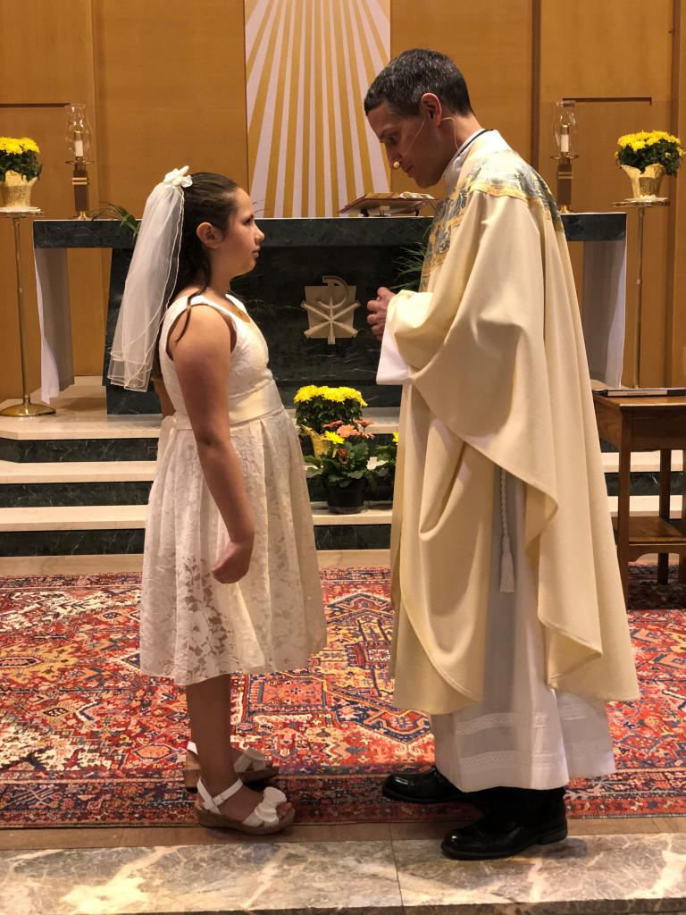 Josephine (left) with Father John Loncle, pastor of Southeast Rochester Catholic Community (St. Boniface, St. Mary and Blessed Sacrament). Josephine received her First Holy Communion at St. Boniface Church. (Submitted by mom, Alexandra)