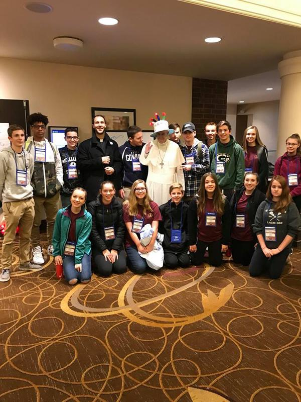 Father David Tedesche and the youth from St. Maximilian Kolbe and St. Joseph the Worker Parishes in Wayne County pose for a photo with a live-size Pope Francis at the Sheraton Indianapolis Hotel at Keystone Crossing. (Photo courtesy of St. Maximilian Kolbe and St. Joseph the Worker Parishes)