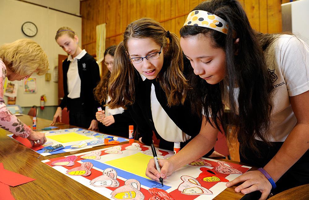 Julia Leahy (C) and Gabby Heisig (R) write a message.