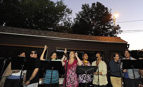 Choir members sing as night falls Aug. 11.
