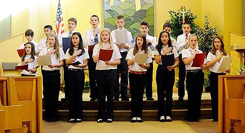 Sixth-graders sing patriotic songs.