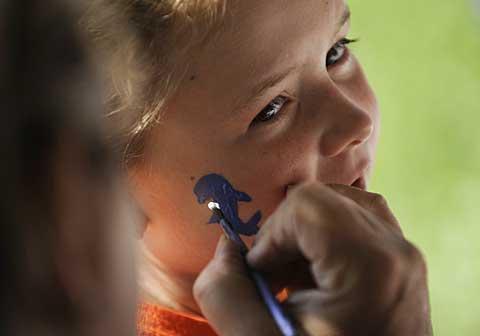 Kindergartner Mackenzie Murphy gets her face painted.
