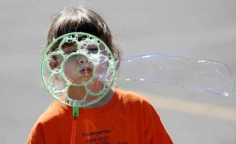 Kindergartner Sarah Kretchmer blows bubbles.