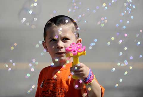 Kindergartner John Labate sends bubbles into the air.