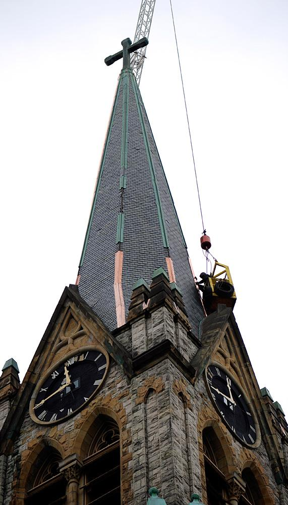 Workers replace copper on the lower part of the steeple.