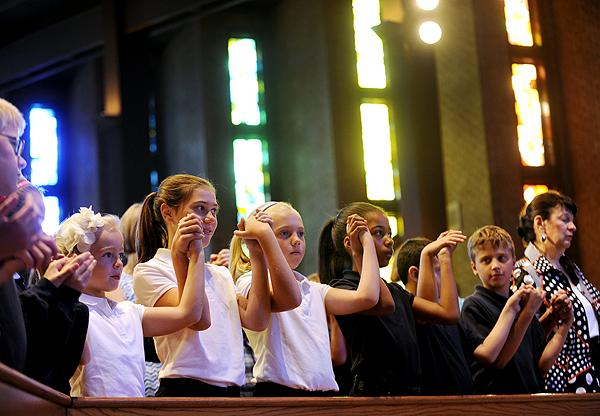 Students join hands during the Lord's Prayer.