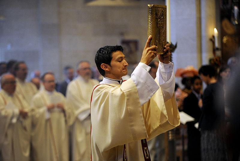 Deacon Sergio Chávez holds the Book of Gospels.