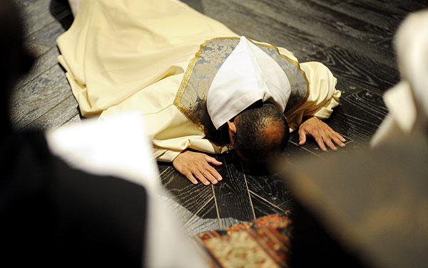 Father D'Souza lies prostrate.