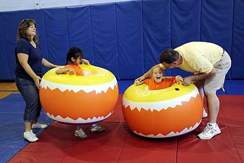 Students bump each other with inflatable donuts.
