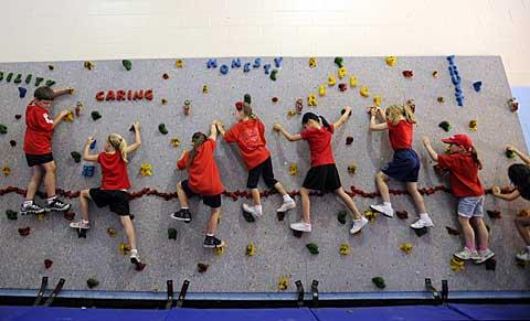 Students scale a portable climbing wall in the gym.