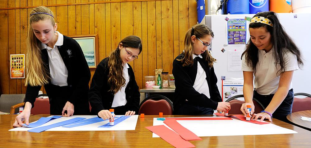 Sixth-graders work on the posters Jan. 23.