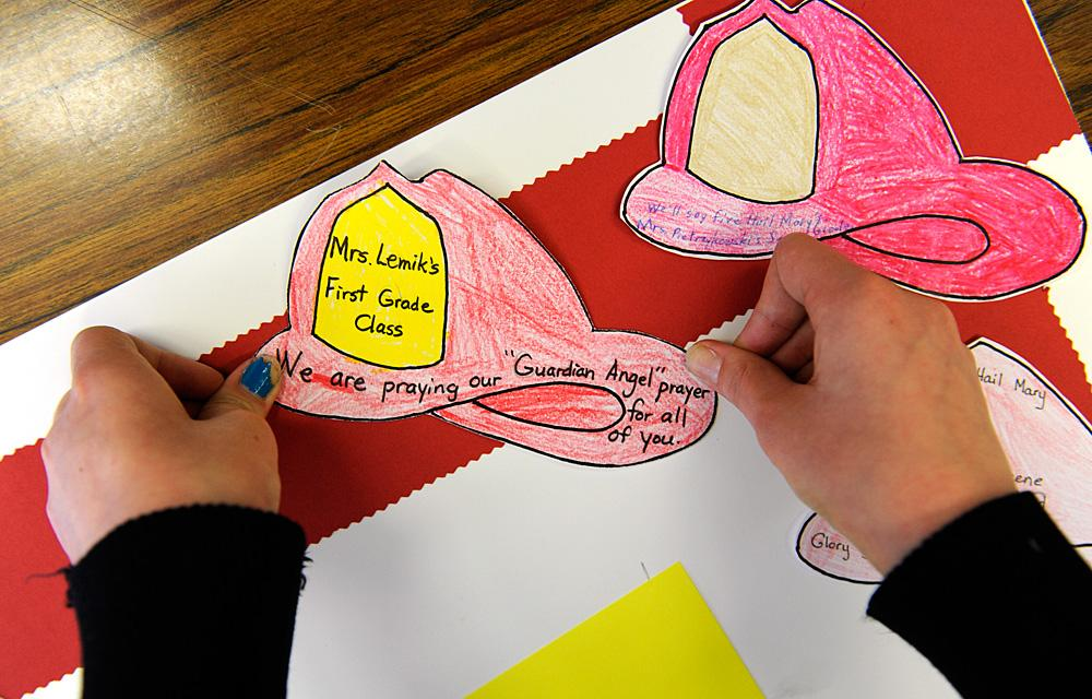 Julia Leahy puts a paper firefighter helmet on the poster.