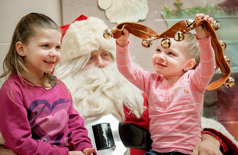 Five-year-old Asyanna Foust (left) and her 3-year-old sister Ayrabella enjoy their visit with Santa Claus during breakfast with Santa Dec. 7.