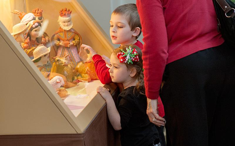 Six-year-old Logan White and his 3-year-old sister Audrey look at some of the nativity sets on display at Sacred Heart Cathedral.