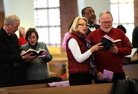 Reg Higgins (R) and his wife Daughn join others in song.