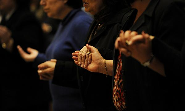 People join hands during the Lord's Prayer.