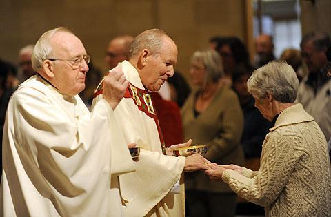 Fr. John Mulligan (L) and Bishop Clark offer Communion.