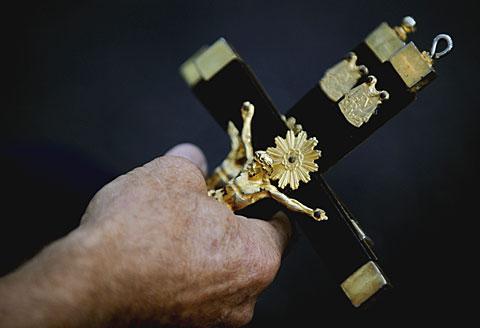 Antonio Quiñones Burgos holds two small crucifixes.